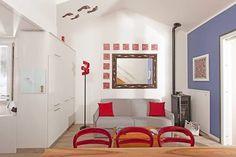 Openspace arredato su misura dal laboratorio di falegnameria #Semprelegno. L'ambiente quasi completamente bianco-grigio è accentuato dall'inserimento delle tonalità di rosso riportate nell'oggettistica decorativa. #madeinitaly #interiordesign #homedecor #fitted #furniture