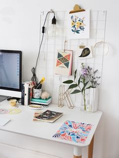 White modern office with computer, flowers and a wire grid note board