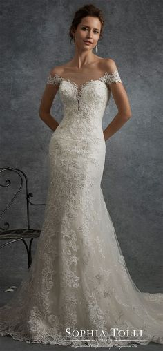 Off-the-shoulder lace fit and flare wedding dress. Misty tulle and allover lace gown adorned with hand-beaded lace appliqués, plunging sweetheart bodice, low illusion back adorned with lace features zipper trimmed with diamante buttons, scalloped lace hem, court length train.