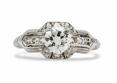Walterboro is a lovely Art Deco engagement ring centering a 0.66ct Transitional Cut diamond accented by diamond studded chevron shoulders. TrumpetandHorn.com | $5,250