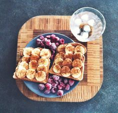 Whole wheat toast with peanut butter, sliced bananas, honey, and cinnamon, with frozen fruit on the side