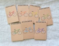 Bike notebook with hand embroidered cover. Listing is for ONE mini-notebook.  Choose from eight different color bike frames, red, orange, yellow, light green, emerald green, light blue, cerulean blue, or purple. If theres another color youd like, send me a message and Ill do my best to accommodate you. Notebook is spiral-bound Japanese stationery, with 50 lined pages. Measures 4 1/8 x 3 1/8 (10.5 cm x 8 cm).  A larger moleskine version of this design is available here…