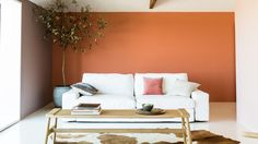 Un salon apaisant alliant des teintes chaudes, comme l'orange cuivre, à des neutres doux et des matières naturelles.