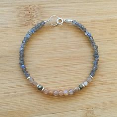"""Faceted labradorite rondelles surround a center of Pyrite and A++ quality peach moonstone beads. The bracelet is 7"""" in length and fastens with a sterling silver spring clasp. Check out more WildGingerJewelry: https://www.etsy.com/shop/WildGingerJewelry?ref=hdr_shop_menu"""
