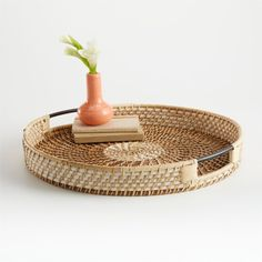 Two tones of rattan—natural and dyed white—weave an ornate tray, supported by a sturdy metal frame. Woven in a circular pattern that reminiscent of a sunflower. Rattan, Wicker Tray, Coffee Table Tray, A Table, Dining Table, Crate And Barrel, Basket Tray, Round Basket, Glass Centerpieces