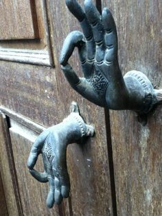 Mudra door handles (mudras are hand signs used in Buddhist figure sculpture) The upturned mudra is the sign of discussion, and the downward one is the sign of compassion and charity.