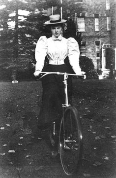 """Young woman on bicycle. Another feature of the 1890s was the emergence of a simple everyday dress for women consisting of a white blouse and simple skirt, usually of darker material. This combination went on right into the 1920s. Here the young woman wears a typical boater-like hat on the top of her head, and her blouse has large """"leg of mutton"""" sleeves."""