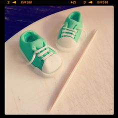 Very small fondant sneakers made as a cupcake topper next to a toothpick to show their size