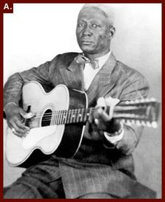 """Alan Lomax took this portrait of Huddie Ledbetter """"Leadbelly"""" with his signature Stella 12 string guitar"""