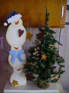Wooden Snowmen Pile with Lighted Tree