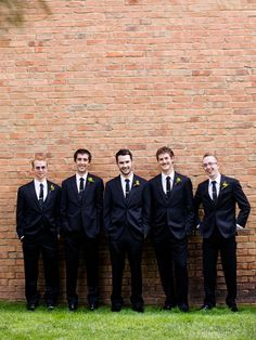 Retro! The groom and his boys give a nod to the '60s with their hip skinny ties and fitted black suits. Cheery yellow boutonnieres are the perfect finishing touch.