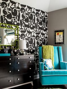 Taupe walls, a bright blue glider and lime green accents balance the black in this dark nursery. Bold black-and-white whale-patterned wallpaper creates a bold focal wall, which is broken up by a solid black dresser.