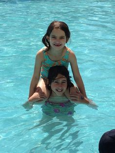 Friends stand next to each other in the pool for a picture, Best Friends sit on each others shoulders! @catherine gruntman Rischer