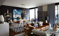 House tour: a vibrant Sydney apartment by Jonathan Adler: An Adler 'Blakely' leather sofa in Lyon Camel with Adler 'Brasilia' cushions is flanked by a gleaming polished brass 'Hans Barbell' side table on one side and playful 'White Horse Head' lamp on the other. Adler's 'Brass Banana' objet d'art appears to recline on the vintage lucite and glass cocktail table, from a New York antiques fair.