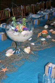 Beach inspired using sand, seashells, and fishing nets.