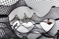 Net Blow-Up par Numen / ForUse Architecture Art Exposition  Voici un projet ludique sur l'architecture exposé à travers une installation itinérante. Cette aire de jeu gonflable dispose d'une grande coquille légère en forme de bulbe qui contient une série de filets tissés à l'intérieur sur plusieurs niveaux.