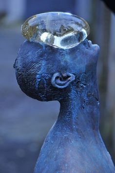 Simple but powerful. A giant raindrop rests on this sculpture's face. (Created by Ukrainian artist Nazar Bilyk.)