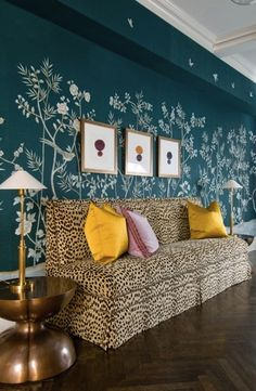 Total knockout deepest teal Gracie paper, leopard sofa, herringbone rug, mid century mod side table, goldenrod velvet throw pillows. Delicious drama in this foyer by Melissa Rufty.