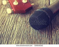 Black microphone on wooden plate with  guitar in out of focus background.: Vintage style and filtered process. - stock photo