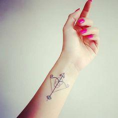 Chica con una flecha del signo sagitario tatuada en su mano