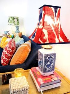 color in mismatched cushions and lamp shades. Books and other small things on side table. by megan