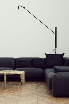 White Walls - Black Sofa - Wall Lamp - Wooden Table - Flooring