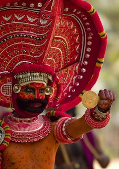 Theyyam dancer in traditional costume with a mirror - India.