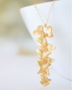 Olive Yew for JEWELMINT COLLECTIVE Orchids symbolize affection, love, luxury, and elegance. All qualities of a lady like you. Adorn yourself with this necklace, and complete your regal look for the garden party. Gold filled chain measures 17 inches, flower bundle measures approximately 2 inches long.This JewelMint Collective piece is made to order just for you by our Collective Designer. Because of the unique design, it takes up to two (2) weeks to create and deliver this piece - and it's…