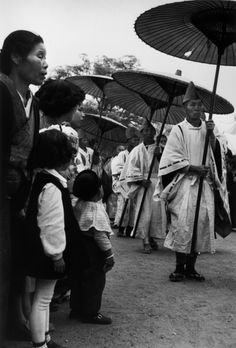 Festival goers watching Monks [?]  Parade with umbrellas. Robert Capa © International Center of Photography Osaka. April, 1954.