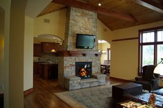 Living room see through fireplace with wood mantel, wood beams, and wood ceiling
