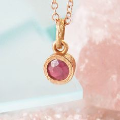 A stunningly simple and elegant pendant necklace featuring a single precious Ruby gemstone in a naturally textured rose gold setting. #Embersjewellery #Jewellery #July #Birthstone #Ruby