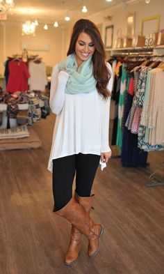 white shirt, black leggings, brown boots, and mint green scarf