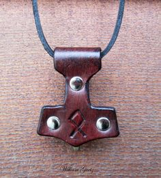 "Leather Mjölnir pendant, measuring 2.5"" tall by 2"" wide"