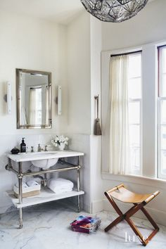 An elegant white and silver bathroom with a leather stool via @thouswellblog