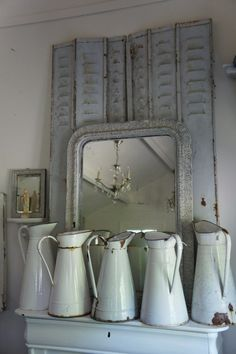 Brocante la Vigne. Iron shutters, antique mirror, chandelier and French white enamel pitchers.