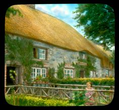 A child in front of a house with thatched roof in Adare.