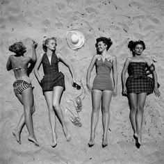Four Models Showing Off the Latest Bathing Suit Fashions While Lying on a Sandy Florida Beach Photographic Print