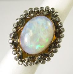OPAL, DIAMONDS AND EIGHTEEN KARAT GOLD RING, featuring a large, single, oval, Australian opal cabochon with blue and green play of color, within a surrounding border of 30 round bezel-set melee diamonds. Estimated to sell between $400-600. To be sold as lot 0214-0052.