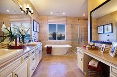 A sleek, freestanding tub adjoins an elegant glass-walled walk-in shower. The Messina plan, built by Toll Brothers, in the Santaluz community. Las Vegas, NV.