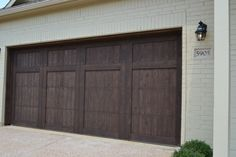 Village Homes: Wood cedar garage door stained in a dark brown. A beautiful accent to the cream painted brick!
