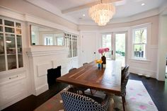 wood table + chandelier + fireplace in dining space by Cardea