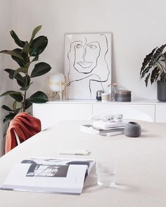 White Scandinavian dining room with line drawing art.  Green plant and deep red are a must this Autumn.  (scheduled via http://www.tailwindapp.com?utm_source=pinterest&utm_medium=twpin)