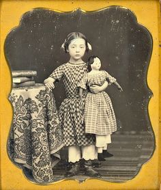 Great daguerreotype of little girl with big shoes and a big doll posed by books.