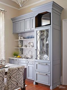 Cherry cabinet doors finished in French blue-gray striate and rubbed with a brushed-pewter glaze provide pretty patina that balances the room's shiny surfaces. A single dishwasher drawer and a 27-inch fridge with freezer drawers pack all the purpose of kitchen requirements into compact units.A small TV tops the fridge cabinet./