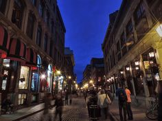 Pedestrians stroll in the yellow glow of the streetlamps that line the cobblestone streets of Vieux Montreal, QC under the deep blue of a twilight sky.