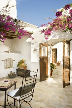 and charming Mediterranean-style patio courtyard, covered in blooming pink bougainvillea.Sunny and charming Mediterranean-style patio courtyard, covered in blooming pink bougainvillea. Spanish Style Homes, Spanish House, Spanish Patio, Spanish Courtyard, Spanish Garden, Outdoor Rooms, Outdoor Living, Outdoor Decor, Rustic Outdoor