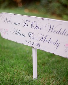 Custom signs from The Back Porch Shoppe welcomed guests to the backyard reception at a friend's cliffside home on Puget Sound. The shabby-chic sign was just one way the couple achieved their vintage, preppy aesthetic.