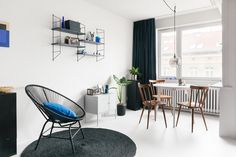 Beautiful small apartment with a small dining area with a white round table, beautiful wooden chairs, a modern pendant light, black string shelves and a black string chair. Check out the whole makeover on our website!