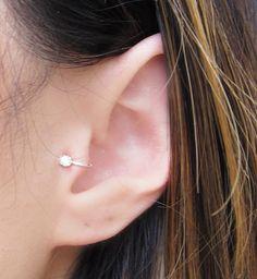 Artikel #SEC300 Funktionen passen eine winzige Ohr-Manschette für den Tragus des Ohres. Um die Ohr-Manschette einzufügen, erstrecken Sie sich die Ohr-Manschette-offen. Dann legen Sie es über den Tragus und drücken Sie die Ohr-Manschette bis dicht auf Ohr. Dies kann auch auf das Ohrläppchen als Clip am Ohrring getragen werden. Alle Metalle sind Silber. -2,5 mm Zirkonia -Passt die meisten Ohren, aber möglicherweise nicht so sicher für diejenigen mit weniger prominent Tragus -Neues Des...