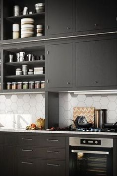 Considering a kitchen makeover by painting your kitchen cabinets a bold color like this black and white kitchen? Would you consider painting your kitchen cabinets black? It's chic and instantly adds drama to any kitchen or bathroom cabinet. Read these tips from 11 designer-approved cabinet paint color ideas that are elegant, everlasting, and aren't white and learn about popular cabinet painting tips, and colors for your Kitchen and Bathroom. Hadley Court Interior Design blog. Interior Design Blog, Painting Cabinets, Cabinet Paint Colors, Kitchen Remodel Small, Kitchen Design, Cabinet, Black And White Decor, Pantry Interior, Home Design Blogs